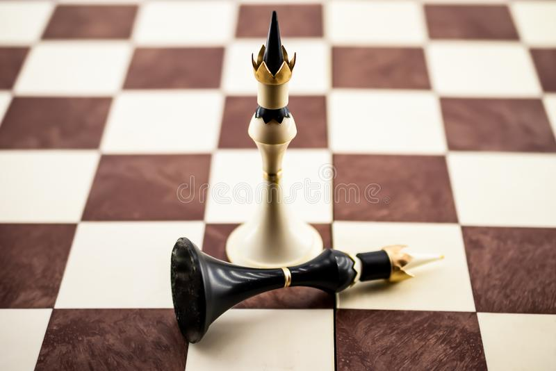 Playing pieces on a chessboard, a white king plunged a black king. Game of figures on a chessboard, the white king has plunged the black king. Suitable for royalty free stock photography