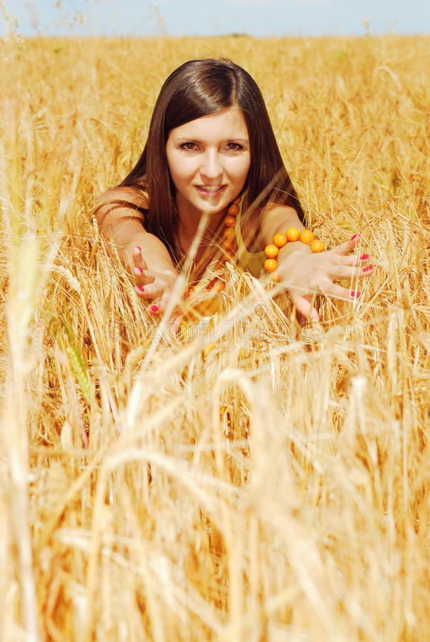 Playing on plant of wheat. Young beautiful woman on plant of wheat stock photography