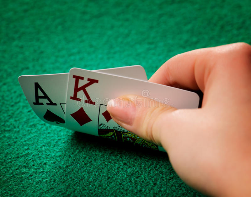 Playing poker. A woman playing poker and looking at her hand stock photos