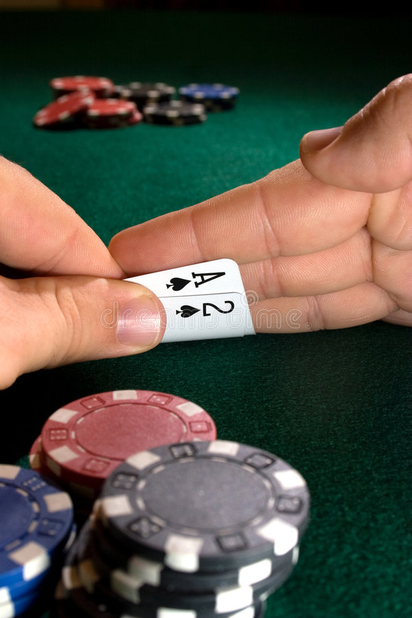 Playing poker. A person playing poker and getting a peek at the cards that were dealt royalty free stock photos
