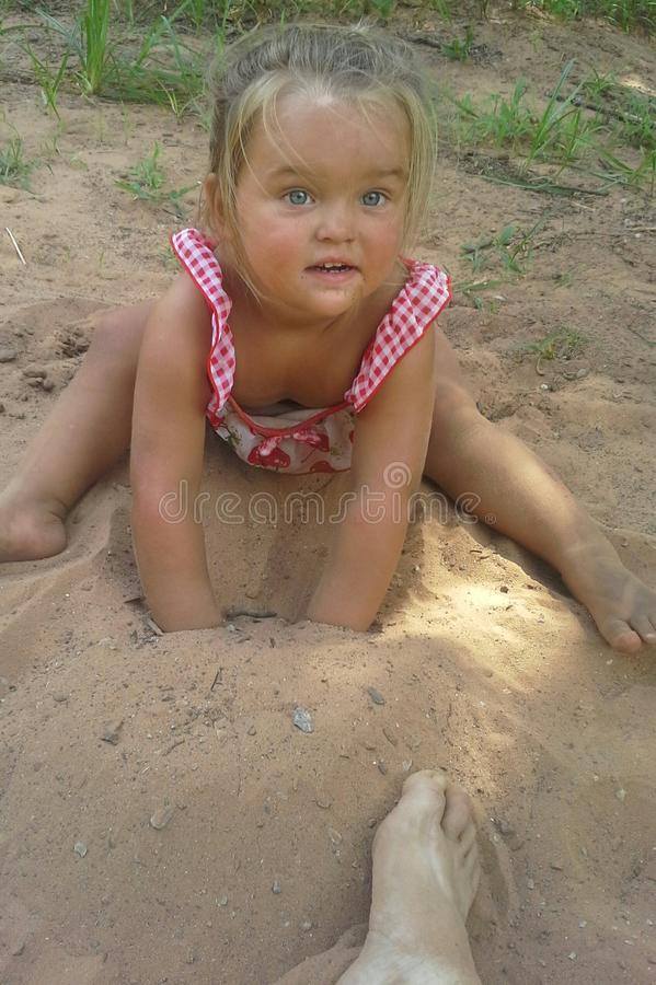 Playing In The Sand. This little, blue-eyed girl is obviously enjoying her playtime burying herself and another`s hands and feet in the cool, summer sand stock photography