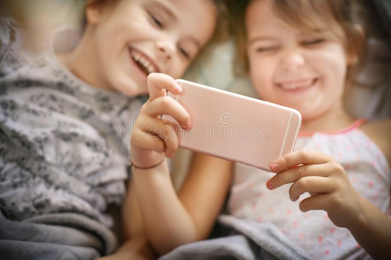 Playing with smart phone. Two little girl using smart phone together. Close up. Focus is on hands stock photo