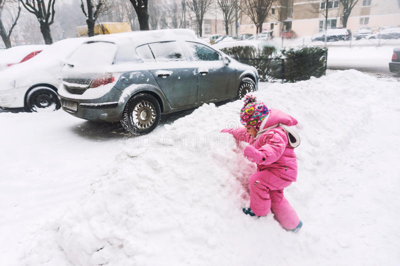 Playing in snow. Small baby girl playing in snow in a city during snowfall royalty free stock photo