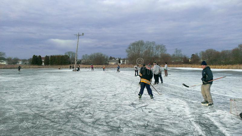 Playing some outdoor pond hockey in the winter. Photo of a group of hockey players on a frozen cranberry pond playing ice hockey stock images