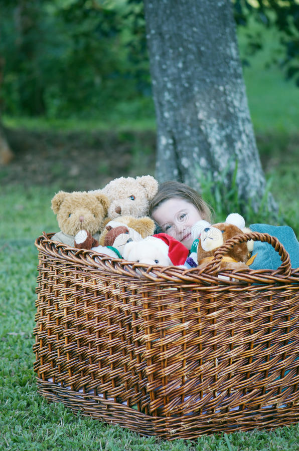Playing with teddy bears. Adorable little girl playing in a large toy wicker basket full of cute teddy bears royalty free stock image