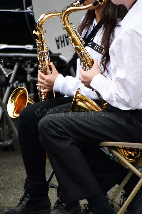 They are playing the tenor sax.  royalty free stock photos