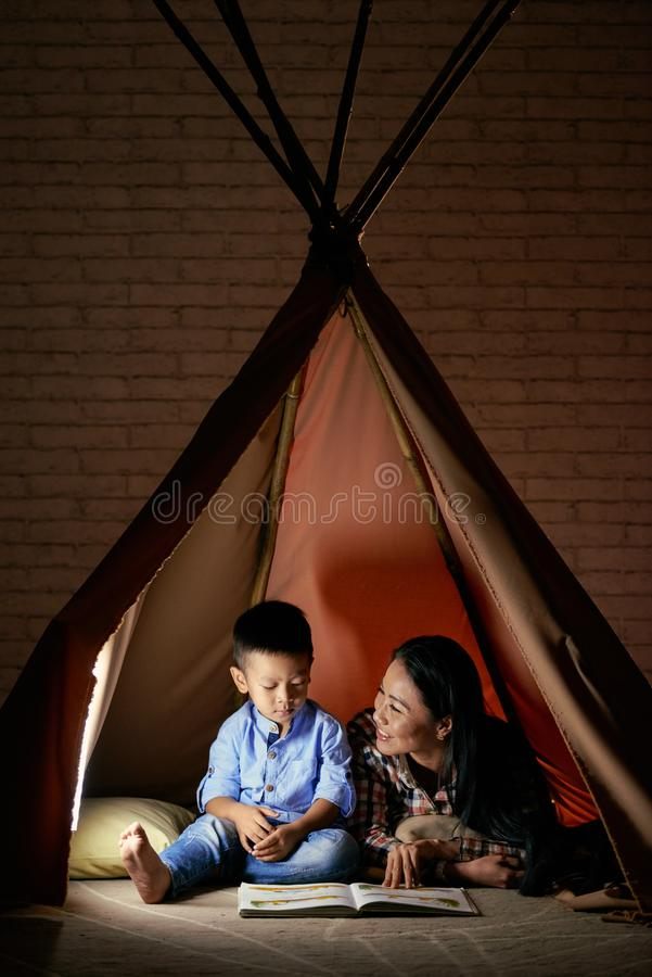 Playing in tent. Mother and son sitting in tent at home and reading a book stock photo