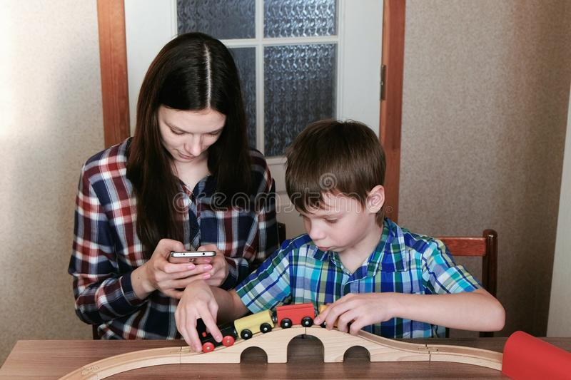 Playing together. Mom looks at phone and son is playing a wooden railway with train, wagons and tunnel sitting at the royalty free stock photos