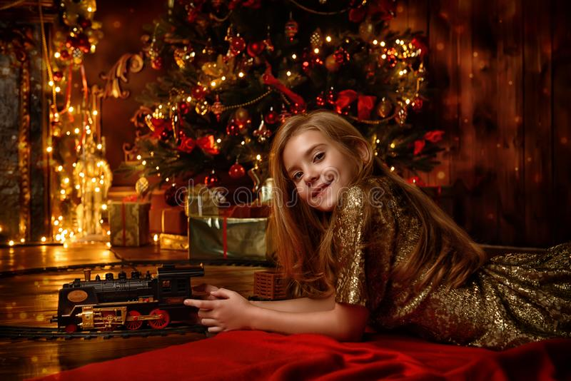 Playing with toy railway. Cute girl playing with a toy railway near the Christmas tree. Christmas night. Christmas decoration royalty free stock photography