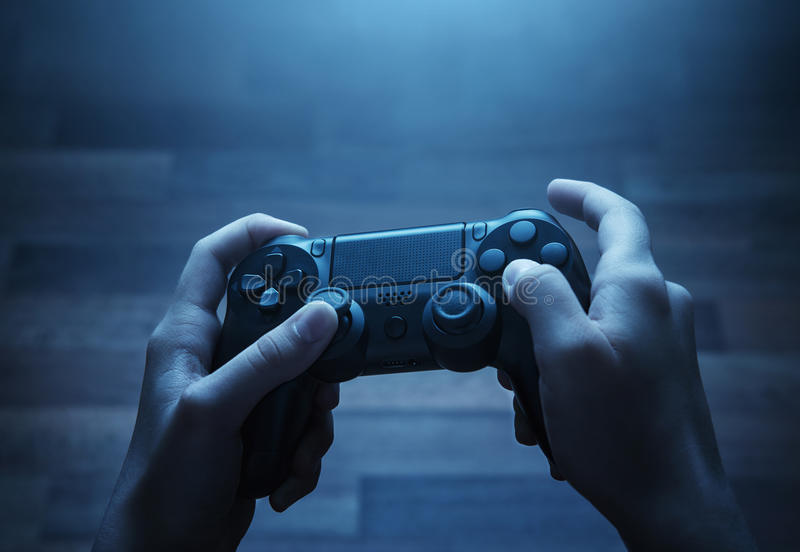 Playing video game. Close up of child hands playing th video game late at night