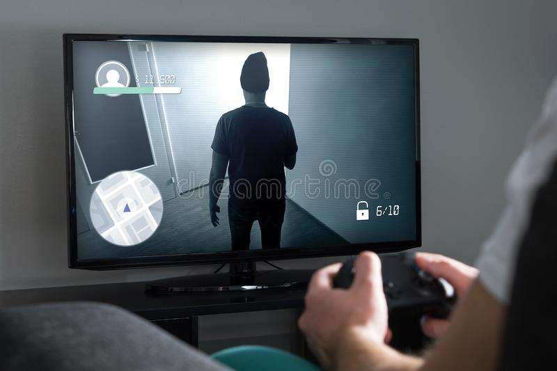 Playing video games at home with console. Gamer with controller. Or gamepad in hand. Young man and TV with action game on screen stock images