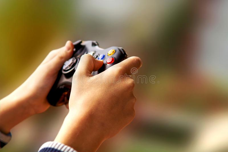 Playing video games on Xbox console. Teenager hands holding Xbox 360 console joystick, playing video games. Finger pushing button. PC gaming device royalty free stock photo