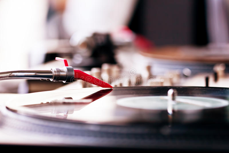 Playing vinyl. Vinyl record spinning on DJ player royalty free stock photo