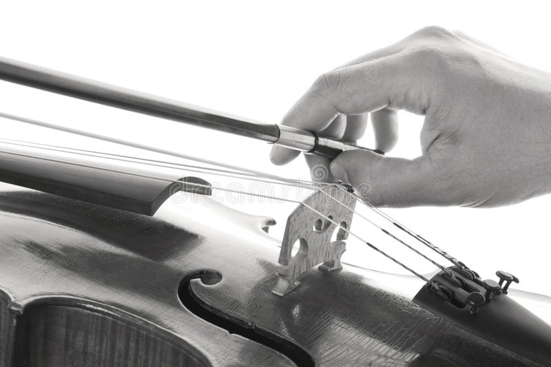 Playing the violin. Hand that pulls the bow on the strings of a violin stock images