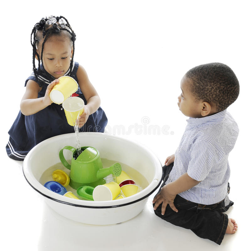 Playing Water Toys in a Tub. An overhead view of two adorable kis playing with toys in a tub of water. On a white background royalty free stock photography