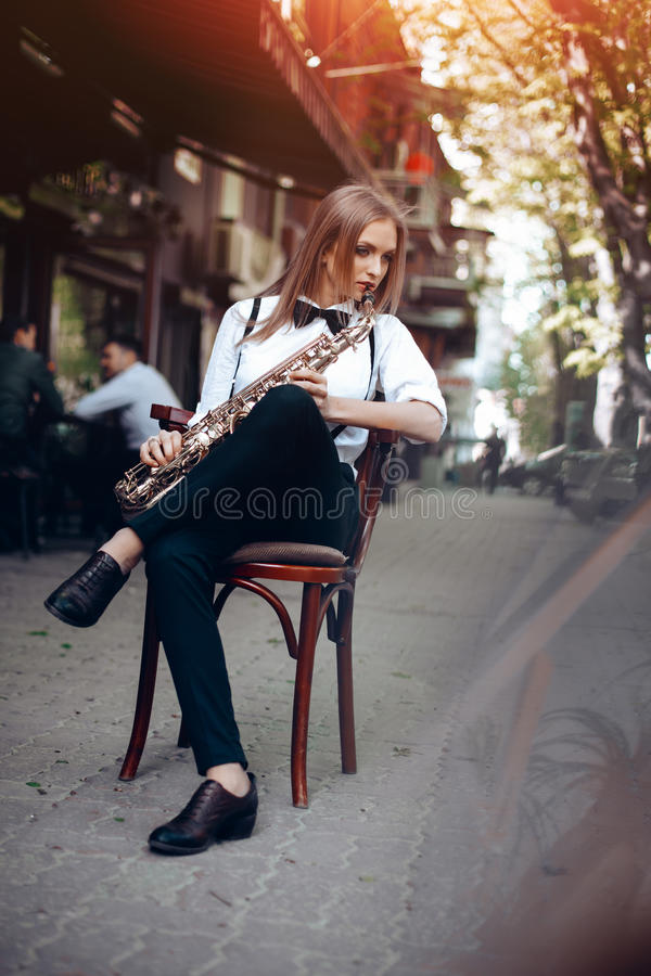 Playing young attractive girl in white shirt with a saxophone sitting near caffe shop - outdoor in sity. young woman with sax royalty free stock photo