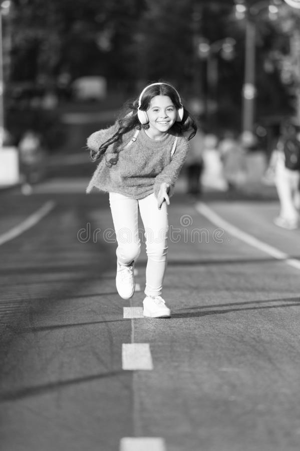 Playlist for active day. Girl cute with headphones. Little child enjoy activity. Kid walking running in park listening royalty free stock images