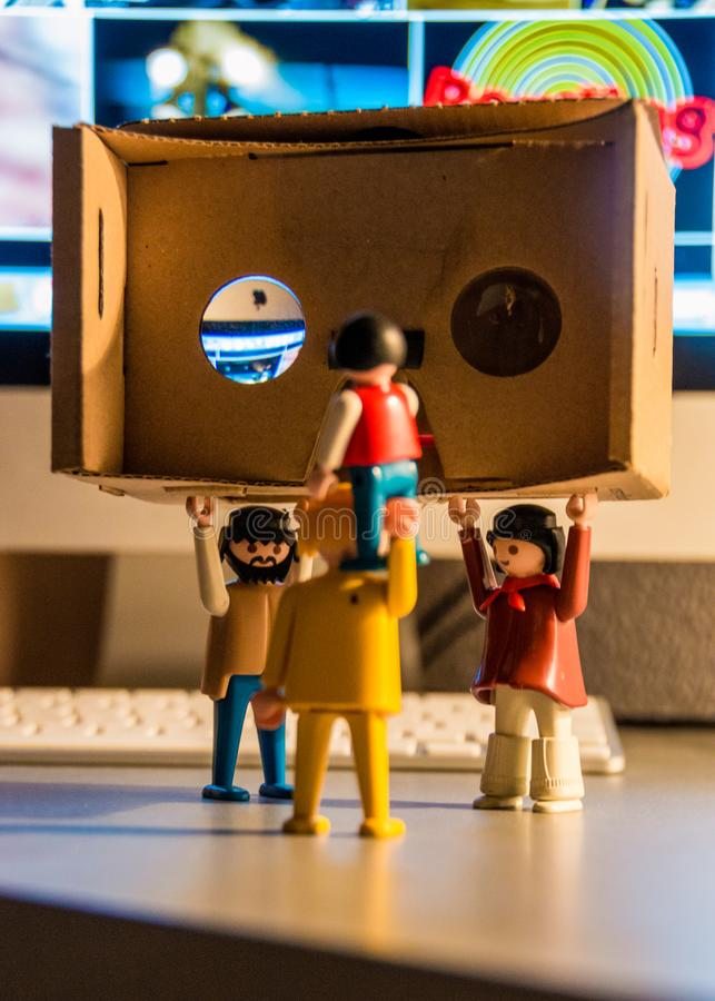 Playmobil playing with google cardboard 3D glasses. stock images