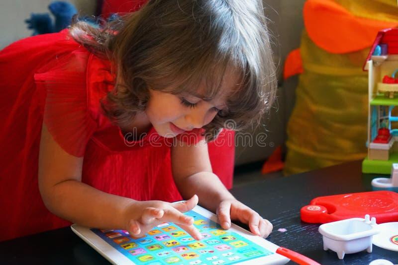 3-4 playng della ragazza di anni con il suo primo computer fotografia stock