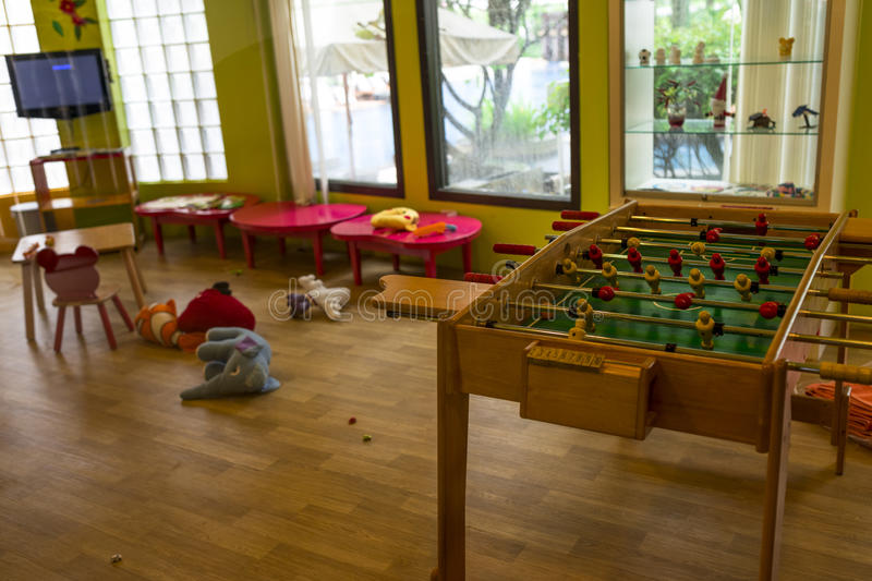 Playroom. Children playroom with table football and soft toy lying on wooden floor royalty free stock photo
