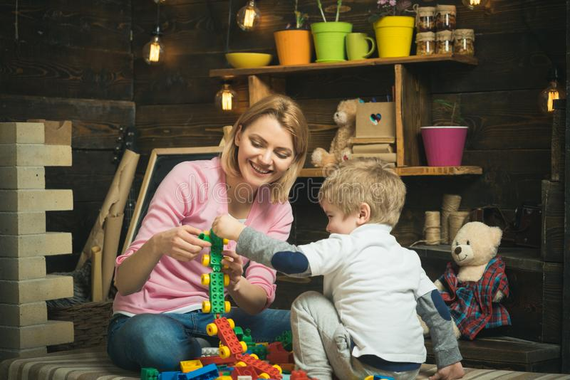 Playroom concept. Playroom is where imagination go wild. Mother and child play with toy bricks in playroom. Mother and. Son build structure model in playroom royalty free stock photography
