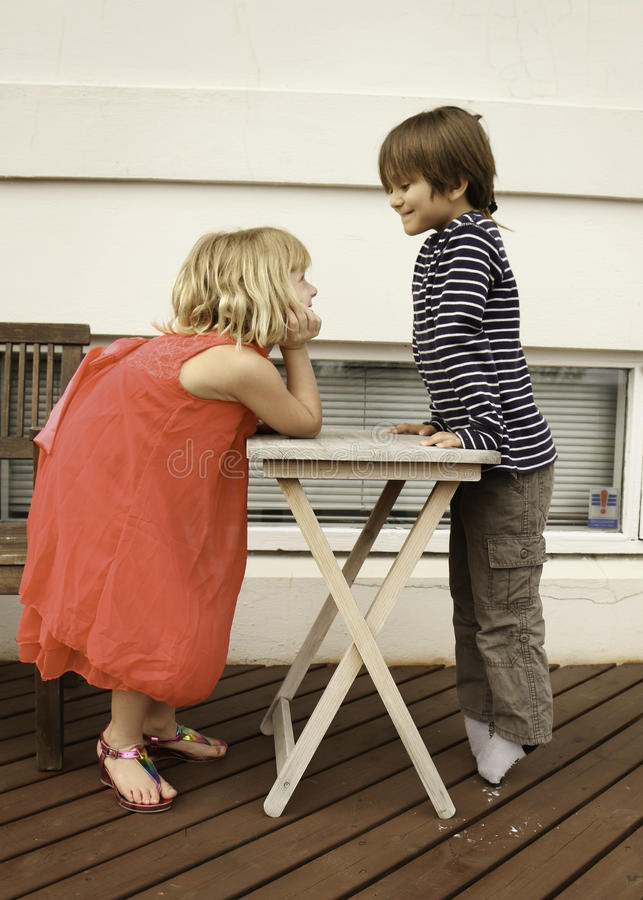 Playtime. Girl and a boy having fun playing and posed around a wooden table stock image
