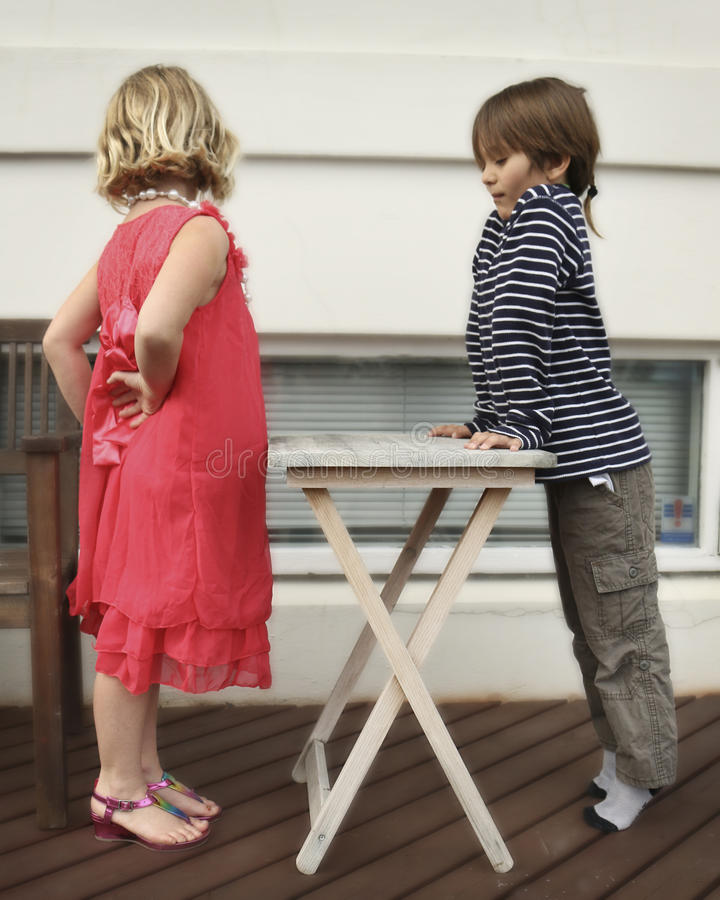 Playtime. Girl and a boy having fun playing and posed around a wooden table stock photography