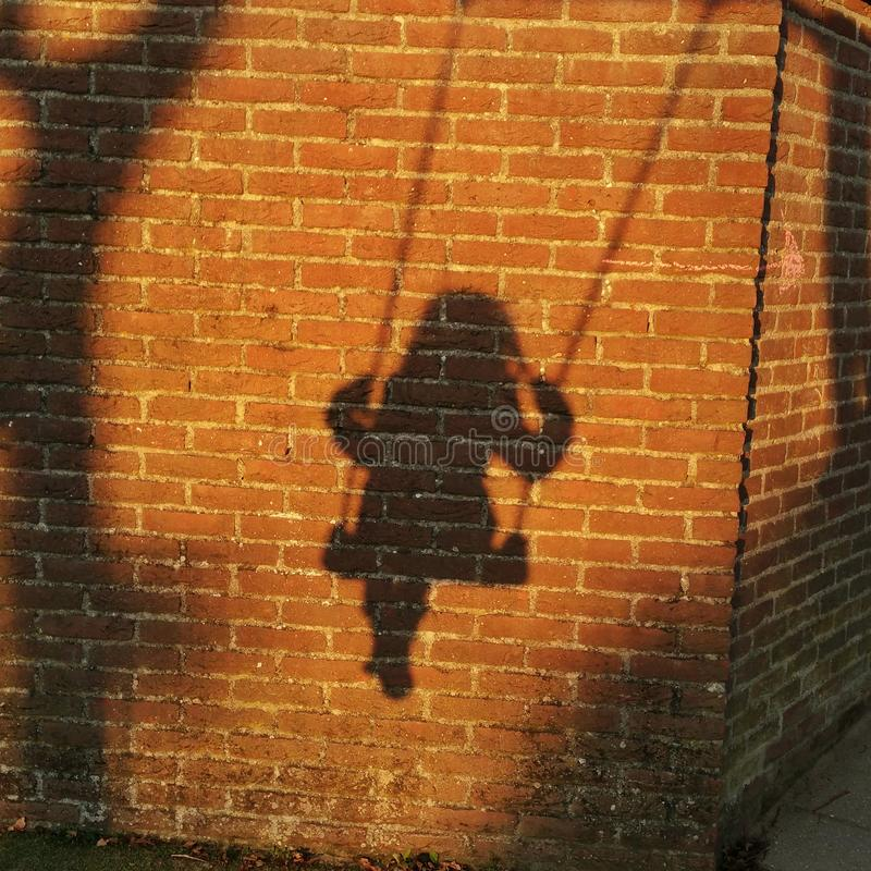 Playtime. Shadow of a child on a swing stock photography