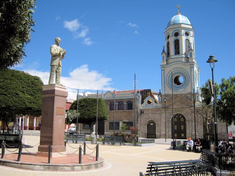Plaza and Cathedral in city El Tambo - Ecuador. Plaza - square and Cathedral in the city of El Tambo - blue and white church tower and dome - with statue Al royalty free stock image