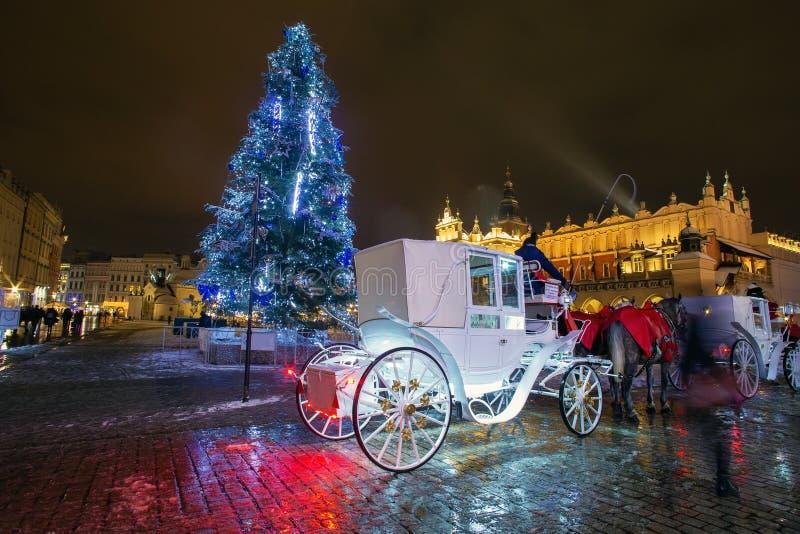 Plaza principal del mercado en Cracovia. invierno nocturno. Carros tirados por caballos imagen de archivo libre de regalías