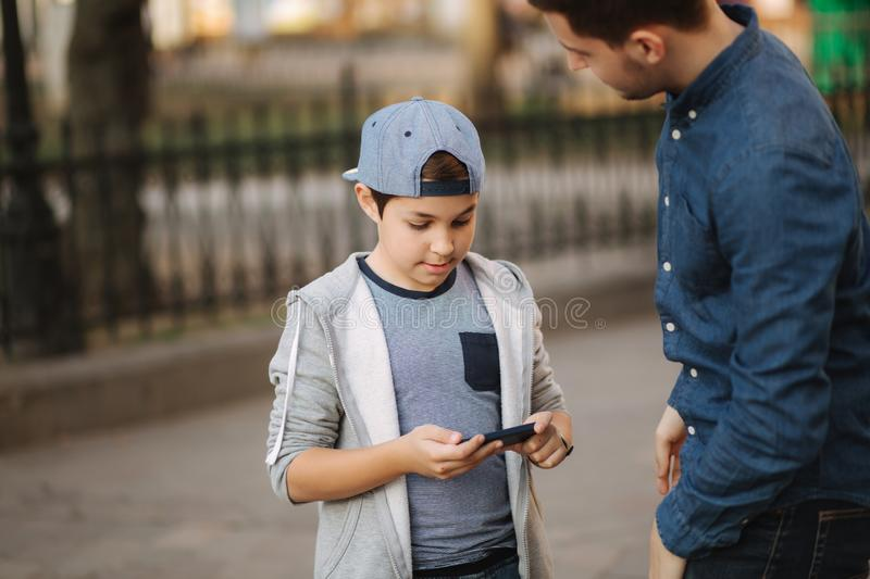 Plder brother explain to younger how to use phone royalty free stock images