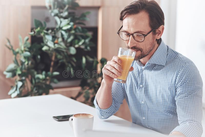 Pleasant adult man drinking juice in the morning royalty free stock photography