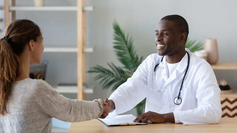 Pleasant african american male doctor shaking hands with patient. royalty free stock photos
