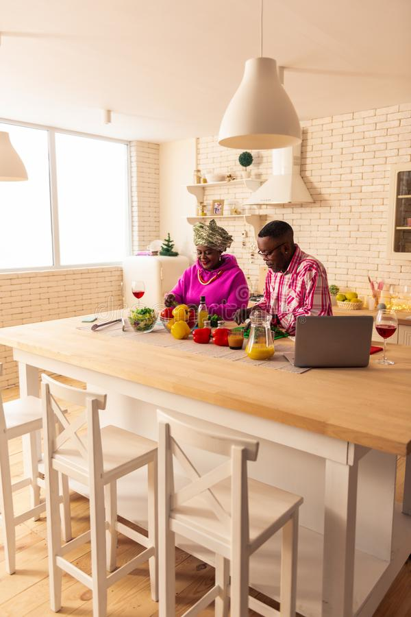 Pleasant African couple cooking their traditional food. Our traditions. Pleasant African couple being in the kitchen while cooking their traditional food stock photography