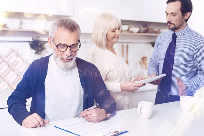 Pleasant aged man signing contract in the kitchen royalty free stock photo