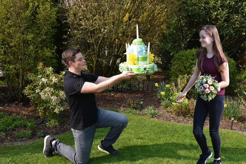 Boy gives flowers  and birthday gift to his girlfriend. Pleasant anticipation, boy kneels in front of his girlfriend and gives her a bouquet of flowers and a stock photos