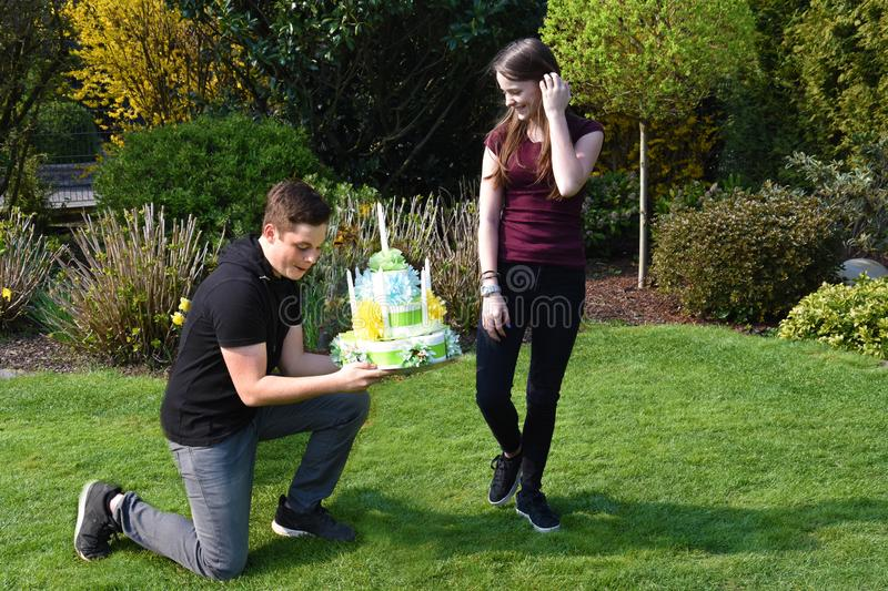 Boy gives  birthday gift to his girlfriend. Pleasant anticipation, boy makes a joke and  kneels in front of his girlfriend and gives her a birthday cake made of stock photos