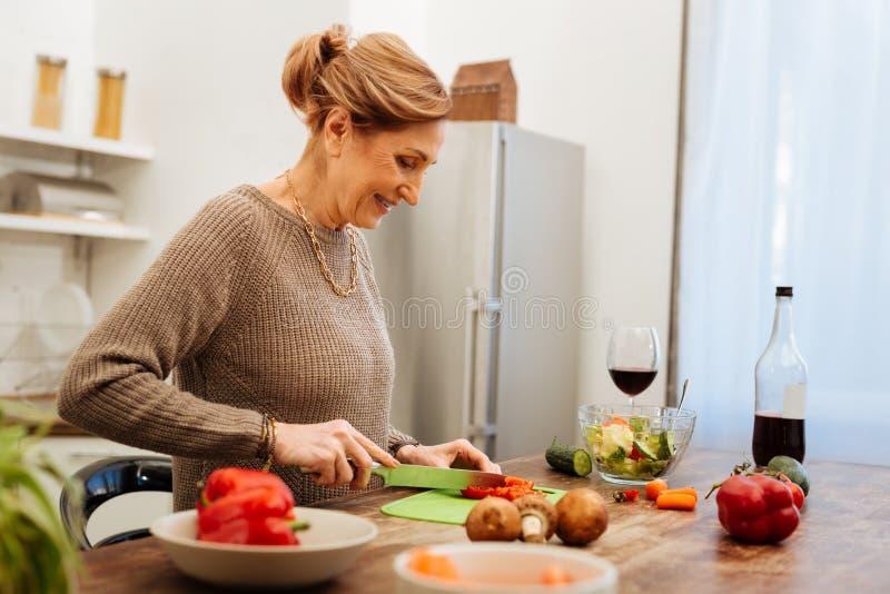 Pleasant attentive mature lady chopping mini carrots stock image