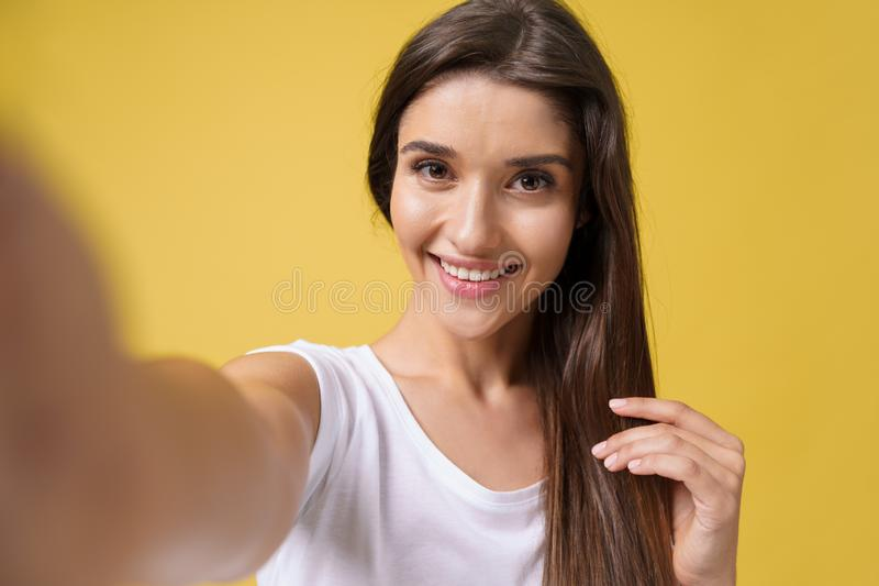 Pleasant attractive girl making selfie in studio and laughing. Good-looking young woman with brown hair taking picture stock photography