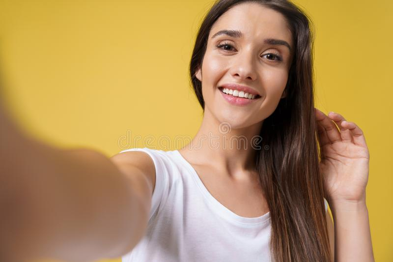 Pleasant attractive girl making selfie in studio and laughing. Good-looking young woman with brown hair taking picture royalty free stock photography