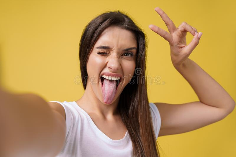 Pleasant attractive girl making selfie in studio and laughing. Good-looking young woman with brown hair taking picture stock photos