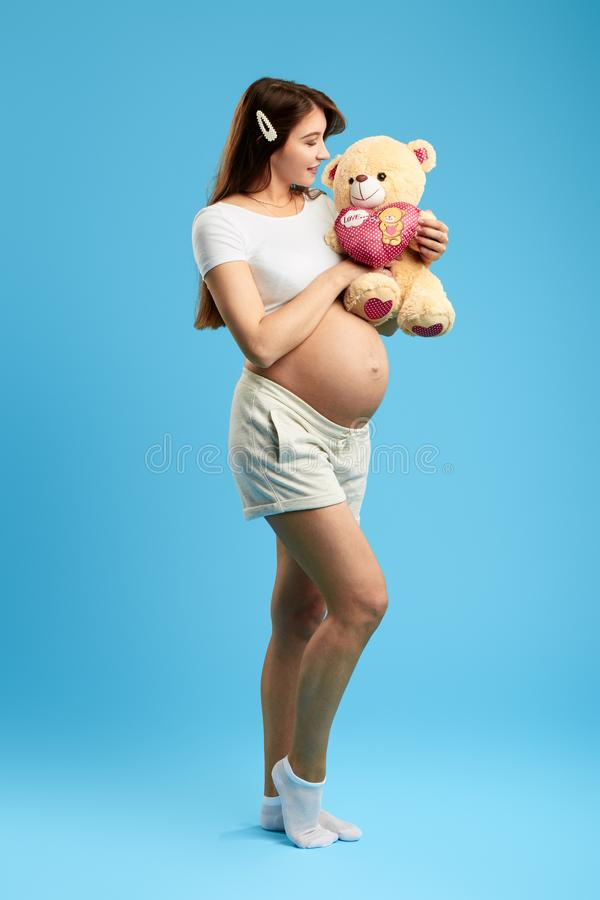 Pleasant attrctive woman with a big belly olaying with teddy bear. Full length photo. isolated blue background. studio shot. entertainment concept stock image