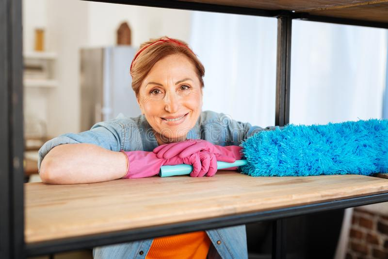 Pleasant beaming mature female leaning on wooden shelf stock photo