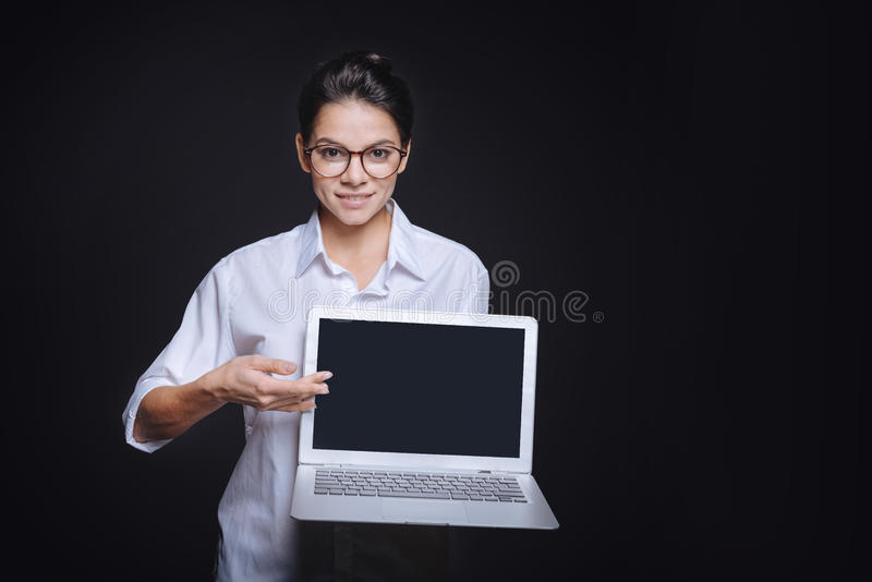 Pleasant beautiful woman showing the laptop to the audience. Look at this. Positive smiling young woman holding the laptop and standing isolated in a black stock image