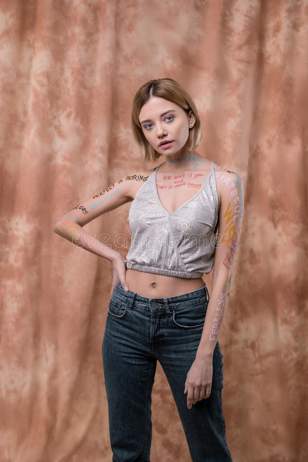 Pleasant beautiful young woman supporting feminist movement. Freedom for women. Pleasant beautiful woman posing for a photo while supporting feminist movement stock image