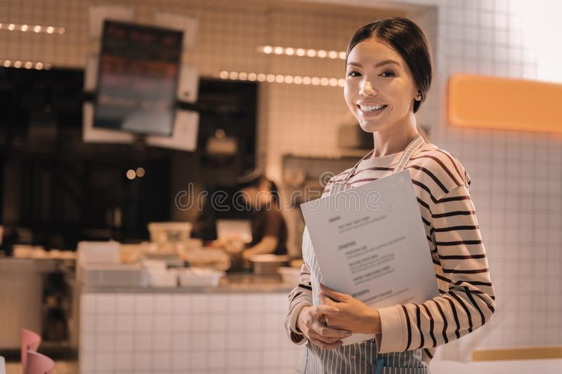 Pleasant beautiful young woman working as a waitress in cozy cafeteria. Beautiful waitress. Pleasant beautiful young woman wearing striped shirt working as a stock images