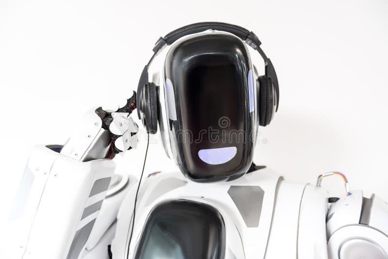 Pleasant big robot is wearing headphone stock photography