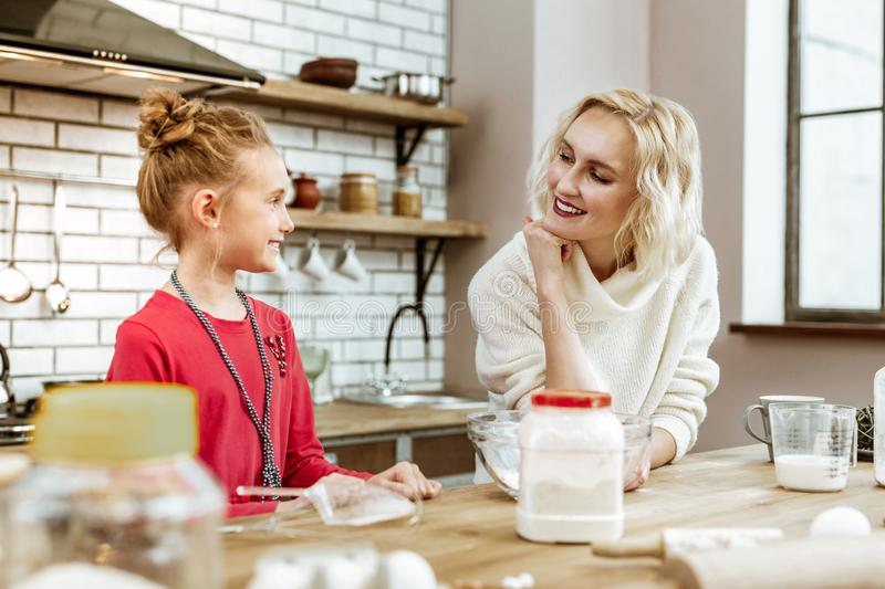 Pleasant blonde lady leaning on her hand while staring on little girl stock photo