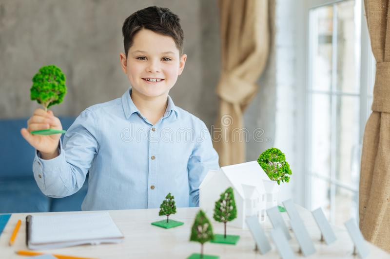 Pleasant boy posing with miniature tree models. Involved in project. Upbeat pre-teen boy sitting at the table full of different miniature models and posing for stock images
