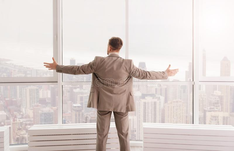 Pleasant businessman enjoying the view from his office royalty free stock images